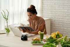 Looking for good recipe online. Young woman searching for recipe to cook for her blog Stock Images