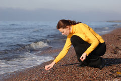 Young woman on a seaside. Young woman looking for an amber on a seaside Stock Photos