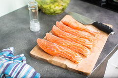 Young woman seasoning a salmon filet Stock Photography