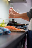 Young woman seasoning a salomn filet in her modern kitchen, Royalty Free Stock Photo