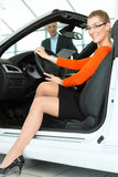 Young woman in seat of auto in car dealership Royalty Free Stock Image