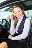 Young woman in seat of auto in car dealership Stock Photos