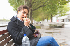 Young woman seated on a bench having lunch in London Royalty Free Stock Images