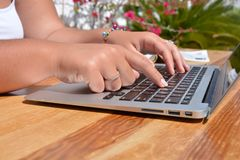 Typing on a laptop keyboard. Young woman seated at a table outdoors, working on a laptop computer, typing on keyboard royalty free stock photo
