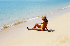 Young woman seating down on a sandy beach and sun bathing Royalty Free Stock Images