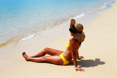 Young woman seating down on a sandy beach and sun bathing Stock Images