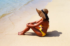 Young woman seating down on a sandy beach and sun bathing Royalty Free Stock Photo