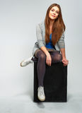 Young woman seating on guitar amplifier. Stock Photos