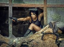 Young woman is a secret agent with a gun in a ruined city. A beautiful girl with a gun in a ruined city. Young female secret agent with braided hair in shorts Stock Images