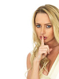 Young Woman With a Secret. A DSLR royalty free image, of an attractive young woman with blonde hair, being secretive with her finger to her mouth, looking Royalty Free Stock Photo