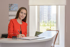 Young woman Secretary in office-stamps to documents royalty free stock photos