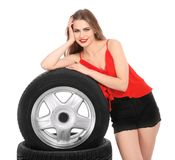 Young woman in seductive outfit with car tires. On white background Stock Images