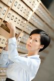 Young woman seeks something in card catalog Stock Image