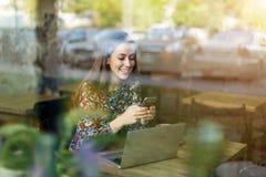 Woman seen through cafe window. Young woman seen through cafe window stock photo