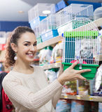 Young woman selecting birdcage for parrot Stock Images