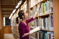 Young woman selecting book in library Royalty Free Stock Images