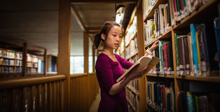 Young woman selecting book in library Royalty Free Stock Image