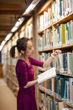 Young woman selecting book in library Royalty Free Stock Photo