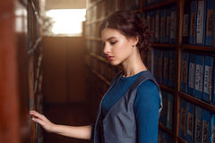 Young woman selecting book from library shelf. Stock Photography