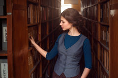 Young woman selecting book from library shelf. Stock Images
