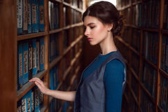Young woman selecting book from library shelf. Royalty Free Stock Photo
