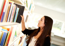 Young woman selecting a book to read. Standing in front of a bookcase pulling a large hardcover volume off the shelf, profile view Royalty Free Stock Photos