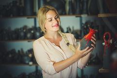 Young woman selecting ceramics with red enamel in atelier Royalty Free Stock Photos