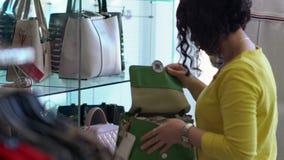 Young woman selecting a green handbag off a shelf