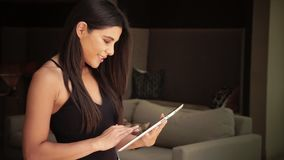 Young woman selecting her entertainment by using swiping tablet. Young woman using swiping tablet and smiling happily stock video footage