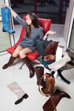 Young woman selecting shoes. Young woman selecting right pair of shoes Royalty Free Stock Photos