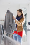 Young woman selecting sweater in store Royalty Free Stock Photo