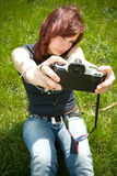 Young Woman Self Portrait. Redheaded young woman dressed casually and sitting on grass, holding a camera out in front of her to take a self-portrait Royalty Free Stock Photo
