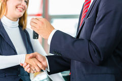 Young woman and seller with auto in car dealership Royalty Free Stock Image