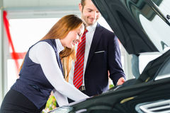 Young woman and seller with auto in car dealership. Seller or car salesman and female client or customer in car dealership presenting the engine performance of royalty free stock photos