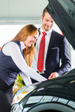 Young woman and seller with auto in car dealership Royalty Free Stock Images