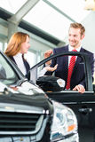 Young woman and seller with auto in car dealership Royalty Free Stock Photos