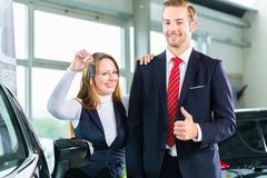 Young woman and seller with auto in car dealership Royalty Free Stock Photography