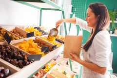 Young woman seller packs dried fruits in the grocery shop stock photo
