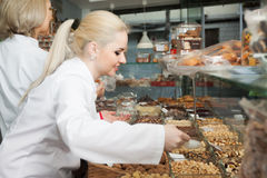 Young woman selling pastry. Portrait of young women selling nuts and pastry in shop royalty free stock images