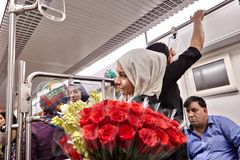 Young woman sells flowers in underground car, Tehran, Iran. Tehran, Iran - April 29, 2017: One muslim girl dressed in hijab, sells flowers of rose inside the Royalty Free Stock Photography