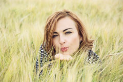 Young woman send a sweet kiss in the wheat field Stock Photo