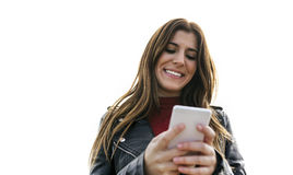 Young woman sending messages with her phone. Portrait of a smiling beautiful young women sending messages with her smartphone Stock Photos