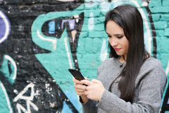 Young woman sending messages with her smartphone. Portrait of a young beautiful woman sending messages with her smartphone. Outdoors Royalty Free Stock Photo