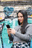 Young woman sending messages with her smartphone. Portrait of a young beautiful woman sending messages with her smartphone. Outdoors Royalty Free Stock Image