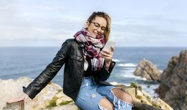 Young woman sending messages. Portrait of a beautiful young woman sending messages with her smartphone on a rocky coast Royalty Free Stock Photography