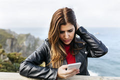 Young woman sending messages. Portrait of a beautiful young woman sending messages with her smartphone on a rocky coast Stock Photos