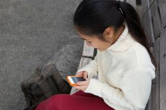 Young woman sending text message on mobile phone Royalty Free Stock Photos