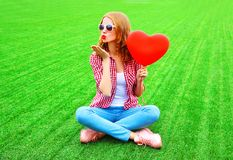 Young woman sends an air kiss with red balloon in the shape of a heart Stock Images