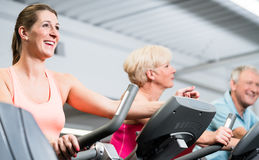 Young woman and senior couple spinning at the gym Royalty Free Stock Photo
