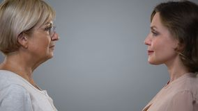 Young woman and senior lady looking each other grey background, aging reflection. Stock footage stock video footage